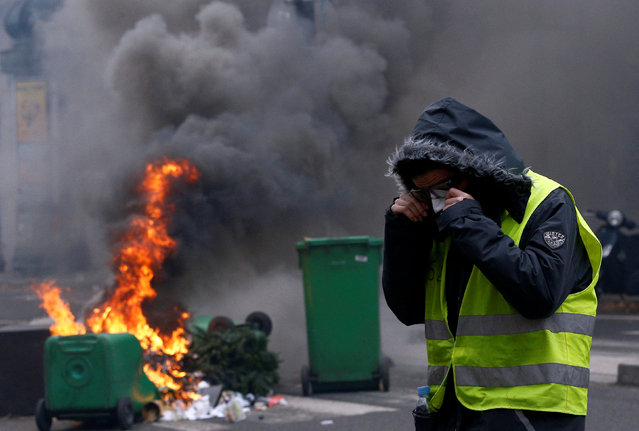 "A protester wearing a yellow vest stands next to burning trash bins in a street during clashes with police at a national day of protest by the ""yellow vests"" movement in Paris, France, December 8, 2018. (Photo by Stephane Mahe/Reuters)"