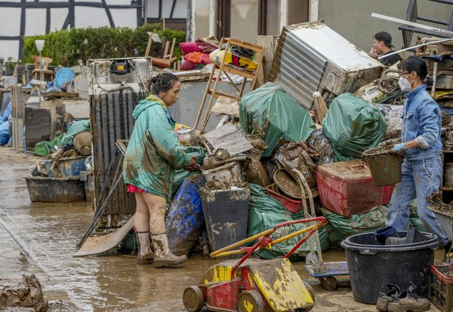 People clean their homes from mud and debris in Bad Neuenahr-Ahrweiler, Germany, Saturday, July 17, 2021. Due to strong rainfall, the Ahr river went over its banks and flooded big parts of the town. (Photo by Michael Probst/AP Photo)