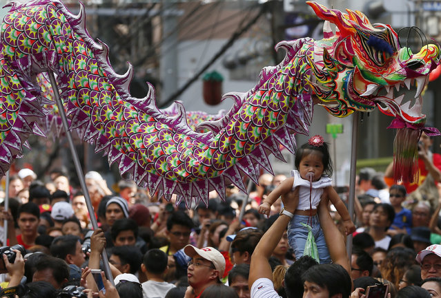 A reveler raises a baby as dragon dancers make their through a crowd to perform in celebration of the Chinese Lunar New Year Monday, February 8, 2016 at Manila's Chinatown district in Manila, Philippines. (Photo by Bullit Marquez/AP Photo)