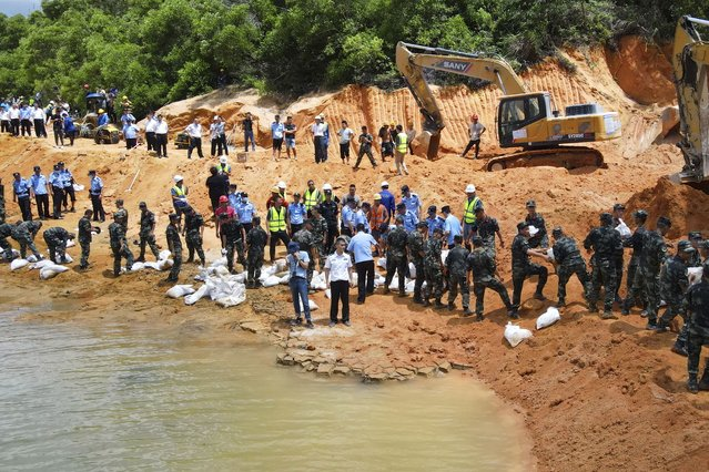 Rescuers work to build an embankment at the site of a flooded tunnel in Zhuhai in southern China's Guangdong Province, Thursday, July 15, 2021. Rescuers were pumping out water Thursday to try to find 14 construction workers trapped by a flood in a tunnel being built in southern China. The rescuers have not been able to contact the workers missing since the 3:30 a.m. flood, the Zhuhai city emergency management department said in an online post. (Photo by Chinatopix via AP Photo)