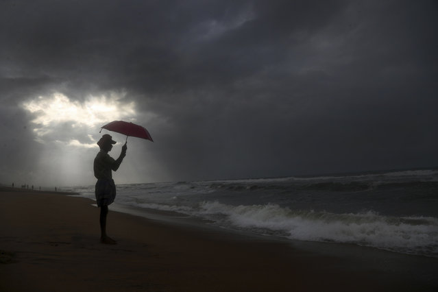 A man holds an umbrella as it rains on the beach by the Bay of Bengal coast in Visakhapatnam, Andhra Pradesh state, India, Thursday, July 15, 2021. (Photo by Mahesh Kumar A./AP Photo)