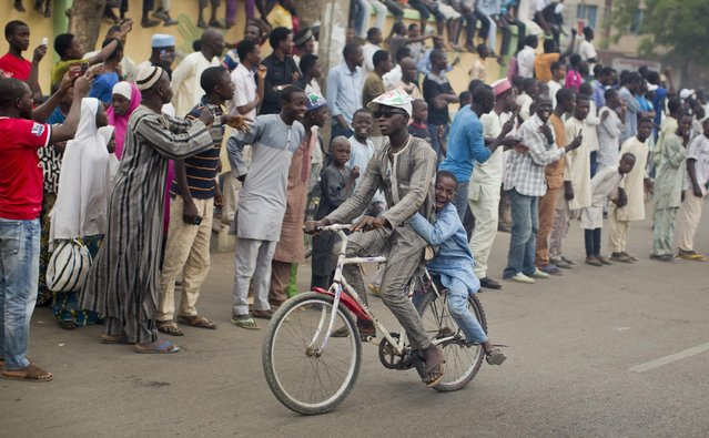 A boy riding on the back of a bicycle shouts out as he passes supporters of opposition candidate Muhammadu Buhari celebrating an anticipated Buhari win in Kano, Nigeria Tuesday, March 31, 2015. (Photo by Ben Curtis/AP Photo)