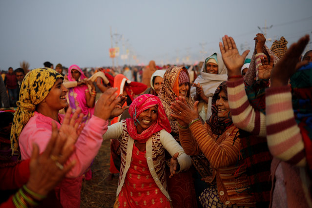 """Devotees sing and dance after taking a holy dip at Sangam, the confluence of the Ganges, Yamuna and Saraswati rivers, during """"Kumbh Mela"""", or the Pitcher Festival, in Prayagraj, previously known as Allahabad, India, January 14, 2019. (Photo by Danish Siddiqui/Reuters)"""
