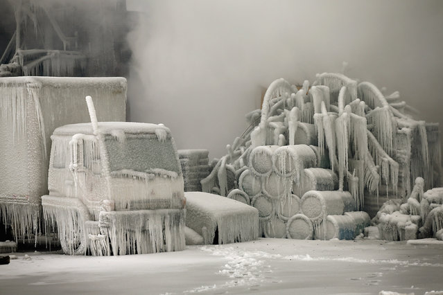 A truck is covered in ice as firefighters help to extinguish a massive blaze at a vacant warehouse on January 23, 2013 in Chicago, Illinois. (Photo by Scott Olson/Getty Images)