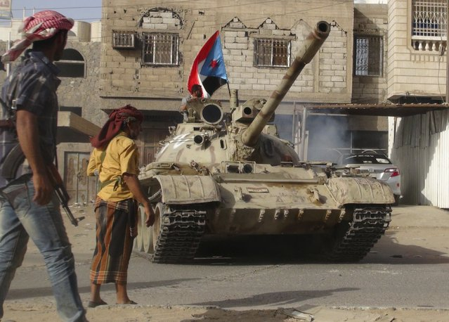 Militants loyal to Yemen's President Abd-Rabbu Mansour Hadi stand by a tank they used in fighting against Houthi fighters in the southern port city of Aden April 11, 2015. Heavy Saudi-led air strikes and ground combat between armed factions battered southern Yemen on Saturday, killing around 20 Iran-allied Houthi fighters and two rival militiamen, residents said. (Photo by Reuters/Stringer)