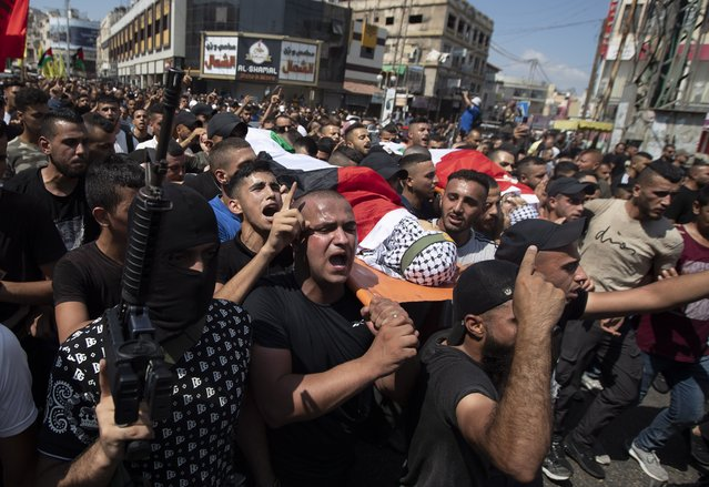 Palestinian mourners carry the body of Raed Abu Seif and Saleh Ammar, two of four Palestinians killed in clashes with Israeli security forces in the early morning, in the West Bank city of Jenin, Monday, August 16, 2021. Israeli troops clashed with Palestinian gunmen during a late-night arrest raid in the occupied West Bank, killing four Palestinians in one of the deadliest battles in the area in years, Palestinian health officials said Monday. (Photo by Majdi Mohammed/AP Photo)