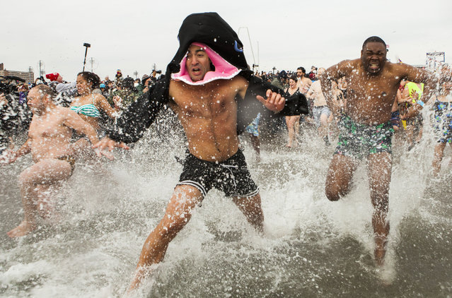 People run into the water just off the Boardwalk January 1, 2014 at Coney Island in the Brooklyn borough of New York City. Hundreds of people gathered for the annual New Year's Day Polar Bear swim in the ocean.  (Photo by Christopher Gregory/Getty Images)