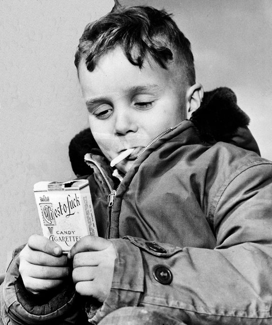 In this March 14, 1953 file photo, Michael Miller, 5, of Fargo, N.D. holds one of his last candy cigarettes in the year North Dakota's governor signed a bill  forbidding the sale or possession of candy packaged to resemble cigarettes. (Photo by AP Photo)