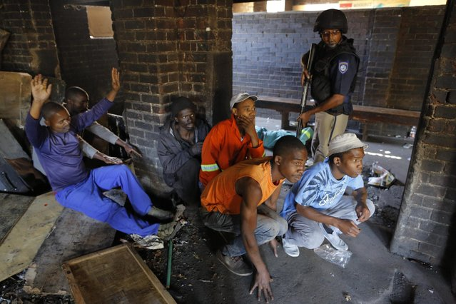 Police officers hold suspects at gun point after they entered mens hostels following xenophobic violence in the area in Actonville, Johannesburg, South Africa, 16 April 2015. Police searched the mens hostels for weapons used by local South African men against foreign African's after five people have been killed during recent xenophobia attacks that started in the South African port city of Durban. (Photo by Kim Ludbrook/EPA)