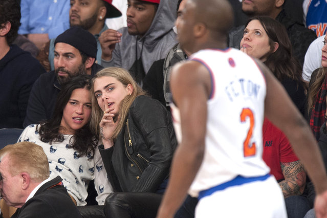 New York Knicks vs Detroit Pistons at Madison Square Garden: Actress Michelle Rodriguez and fashion model Cara Delevingne attend tonights game together seated in the front row. Michelle Rodriguez is visibly seen smoking what appears to be a E-Cigerette. As the game progressed Rodriguez appeared more and more intoxicated. January 7th, 2014. Credit Anthony J. Causi