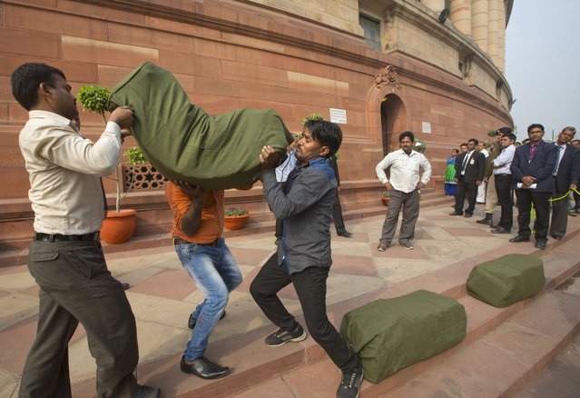 Indian workers carry a bag containing the copies of the federal budget for the year 2016-17, that will be distributed to lawmakers at the parliament house in New Delhi, India, Monday, February 29, 2016. It was Indian Finance Minister Arun Jaitley's second full budget since Prime Minister Narendra Modi won a huge majority in national election in 2014, on the back of promises to turn around the economy and boost job creation. There have been few sweeping reforms in the past two years that the government has been promising. (Photo by Manish Swarup/AP Photo)