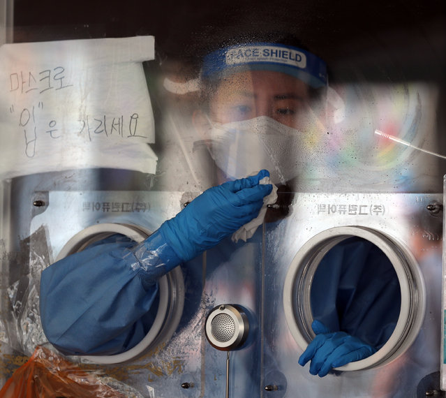 A medical worker prepares to conduct coronavirus tests at a screening clinic in front of Seoul Station, Seoul, South Korea, on 20 July 2021. South Korea's daily new coronavirus cases stayed in the 1,200s for the second consecutive day due to fewer tests amid scorching hot weather, as authorities are tightening their guard against the fast spread of the highly contagious delta variant across the nation. (Photo by Yonhap/EPA/EFE)