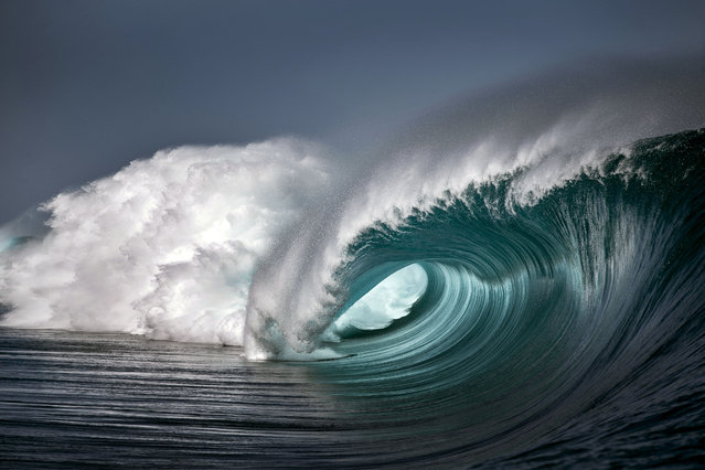 A shot of a wave crashing down into the ocean in the clear waters of Teahupoo. (Photo by Ben Thouard/Caters News)