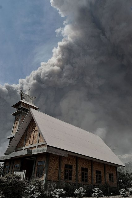Sinabung volcano erupts spewing thick smoke and hot ash as a church is seen on the fore ground in Karo on January 16, 2014. (Photo by Sutanta Aditya/AFP Photo)