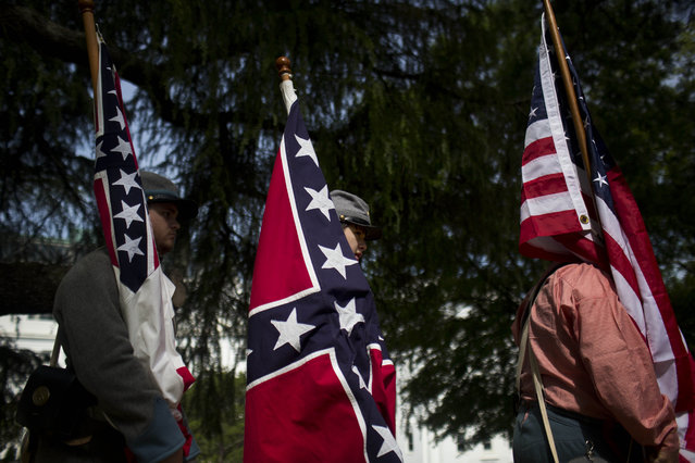 Brandon Grant, of Troy, Ala., left, and Jakan Kyle, of Elba, center, carry confederate flags near the Alabama State Capitol during Confederate Memorial Day, Monday, April 27, 2015, in Montgomery, Ala. (Photo by Brynn Anderson/AP Photo)