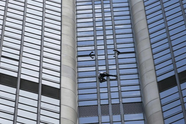 "People take pictures from the window as French climber Alain Robert, also known as ""Spiderman"", scales the Tour Montparnasse, a 210-metre (689 ft) building in central Pairs, France April 28, 2015. Robert scaled the tower carrying a flag of Nepal in support of the victims of the earthquake in Nepal. (Photo by Gonzalo Fuentes/Reuters)"