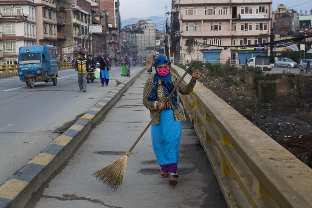 A Nepalese municipal worker cleans the street early morning in Kathmandu, Nepal, Wednesday, April 29, 2015. (Photo by Bernat Amangue/AP Photo)