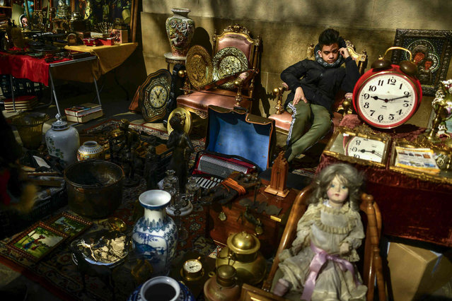 "A young seller waits seated between antiques, in a corner of the old city, while people visit the antiques market ""Pulgas' Market"" in Pamplona northern Spain, Saturday, March 2, 2019. (Photo by Alvaro Barrientos/AP Photo)"