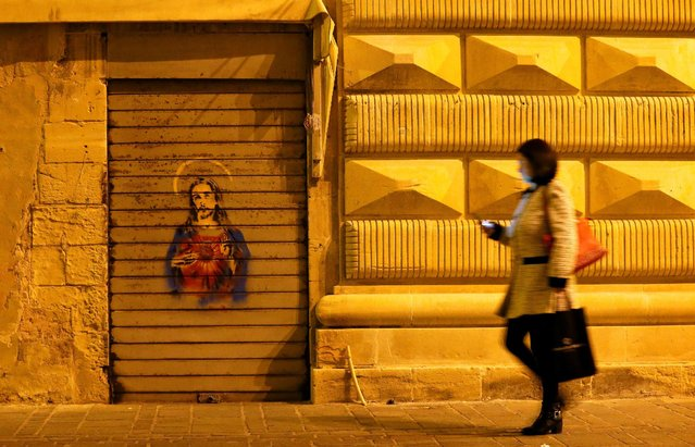 A woman looks at her mobile phone while walking in downtown central Valletta, Malta February 2, 2017. (Photo by Yves Herman/Reuters)