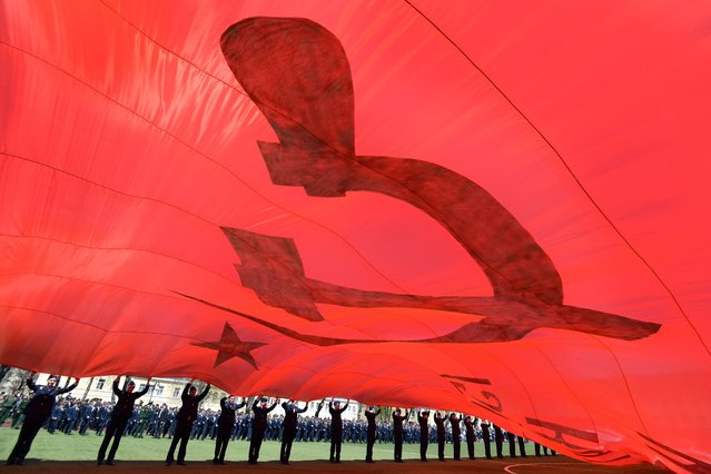 Russian military cadets hold a giant replica of the Soviet Banner of Victory at their college in southern Russian city of Stavropol on April 26, 2015. The cadets created the replica of the banner which was placed over a Reichstag building in Berlin in May 1945 by Soviet troops, to mark the 70th anniversary of the victory in WWII. The replica is 40 meters large and 17.5 meters long. (Photo by Danil Semyonov/AFP Photo)