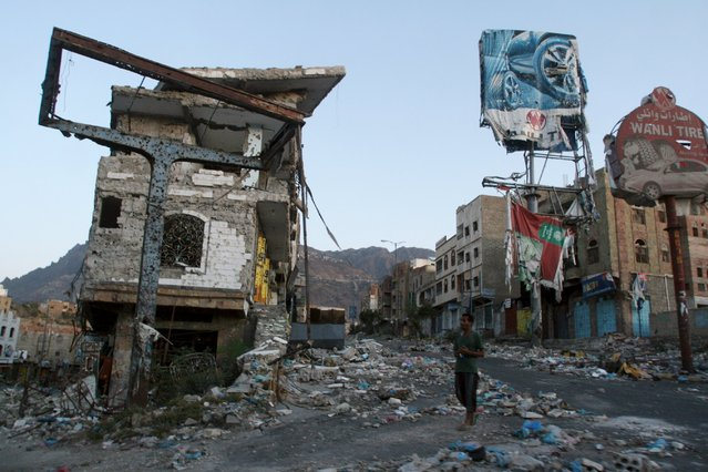 A man walks past a building destroyed during recent fighting in Yemen's southwestern city of Taiz March 14, 2016. (Photo by Anees Mahyoub/Reuters)