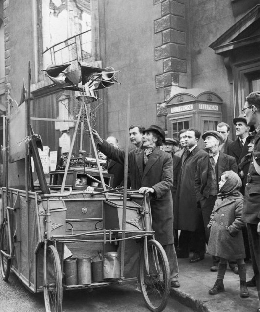 John Dyson, 63-year-old inventor, gets his perfected bomber destroyer, which is mounted on a bicycle cart, ready for a tour of London streets to impress the public, December 15, 1941, since British Government authorities remain indifferent to its potentialities. Mr. Dyson blames the old-school-tie crowd in the Government for the disinterest shown in his working model. Mr. Dyson presses buttons, turns innumerable gadgets, and the steam whistles and something starts turning with squeaks of protests, and gradually the whole business starts whirling and bobbing up and down, and then, according to him, you are witnessing a model of the machine that will save any country from bombers. After lecturing the curious, he asks for coins so that he may continue his research and buy a new alarm clock, as a new clock would help the cause. (Photo by AP Photo)