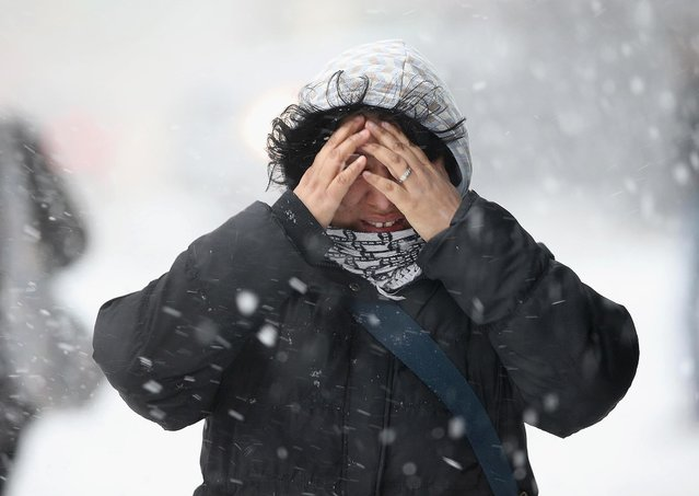 A woman covers her face while walking through the snow in New York City. (Photo by John Moore/Getty Images)