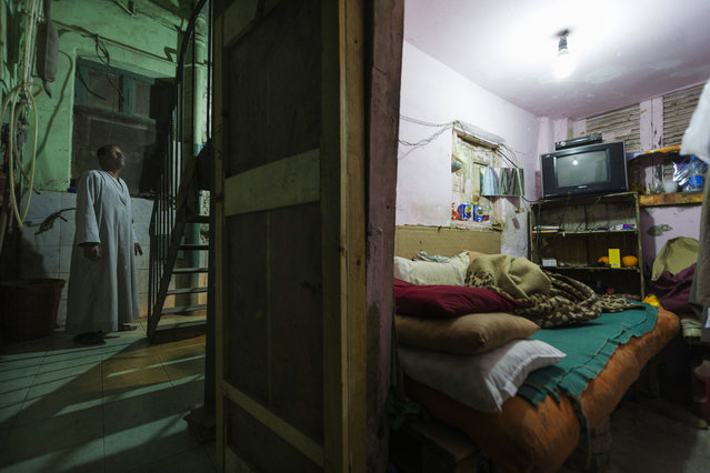 "In this April 25, 2015 photo, Salama Osman waits for water to be boiled to make tea before going to bed in his room, where he lives under the emergency stairs in the back of an apartment building where he works, in Cairo, Egypt. Osman is a ""bawaab"", one of likely tens of thousands of migrant workers across Cairo who function as doormen, car parkers, errand runners, night watchmen, gardeners and just about anything. (Photo by Hiro Komae/AP Photo)"
