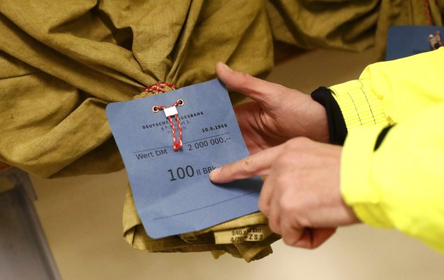 A tour guide displays a money sack showing it contained emergency issue bank notes worth two million German marks, inside a Federal reserve bank (Bundesbank) bunker prior to the bunker's official opening to the public in Cochem, Germany, March 18, 2016. (Photo by Kai Pfaffenbach/Reuters)