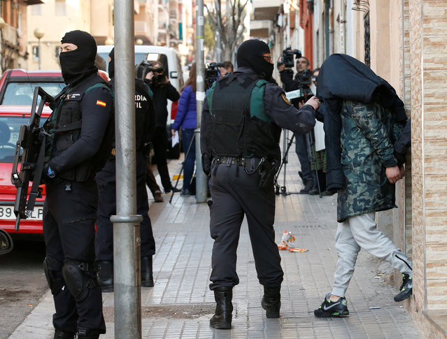 Spanish civil guards escort a detained suspect, accused of recruiting and training potential combatants for the Islamic State, in Badalona, northeastern Spain, February 7, 2017. (Photo by Albert Gea/Reuters)