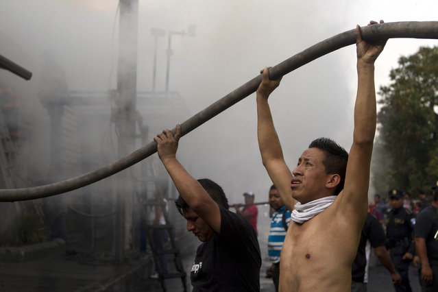 Vendors hold hoses as they help firefighters control a fire in a tire warehouse in La Terminal, the largest and most important market in Guatemala City, Wednesday, May 6, 2015. According to the fire department, firefighters worked for two hours to control the fire that affected several shops. No injuries where reported. (Photo by Moises Castillo/AP Photo)