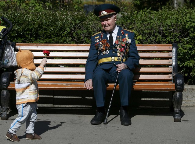 A little girl gives a flower to a blind World War Two veteran during the Victory Day celebrations at Gorky park in Moscow, Russia, May 9, 2015. (Photo by Maxim Zmeyev/Reuters)