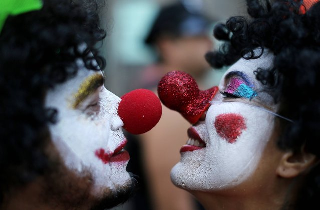 A couple in clown costumes touch noses during the Boitata block party, a pre-Carnival celebration in Rio de Janeiro, Brazil, Sunday, February 23, 2014. People gathered for one of the many parades before the official start of Carnival on February 28. (Photo by Leo Correa/AP Photo)