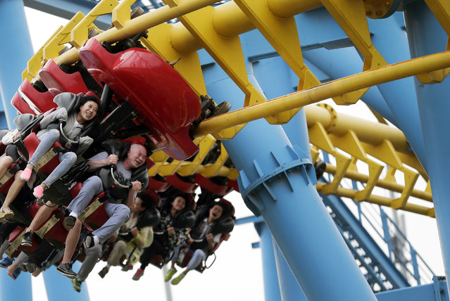 People ride a roller-coaster at Xiedao's theme park during a May Day holiday in Beijing, China, Friday, May 1, 2015. (Photo by Andy Wong/AP Photo)