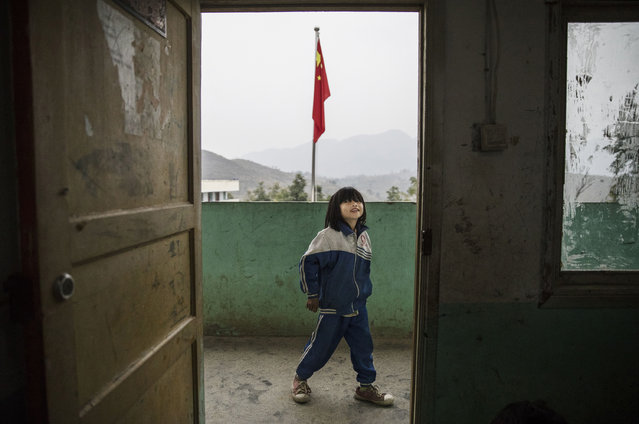 """""""Left behind"""" child  Luo Hongni,11, waits outside her class at a local school on December 16, 2016 in Anshun, China. (Photo by Kevin Frayer/Getty Images)"""