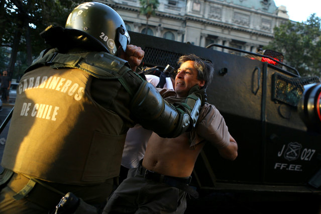 A riot policeman tries to detain a protester during a rally marking the anniversary of the death of union leader Juan Pablo Jimenez, in Santiago, Chile February 21, 2017. (Photo by Ivan Alvarado/Reuters)