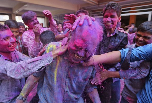 Students apply coloured power onto their teacher's head during Holi celebrations at a school in the western Indian city of Ahmedabad March 14, 2014. Holi, also known as the Festival of Colours, heralds the beginning of spring and is celebrated all over India. (Photo by Amit Dave/Reuters)