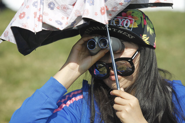 A spectator uses binoculars to watch a play on the 18th hole during the final round of the Volvo China Open golf tournament in Shanghai, China, Sunday, April 26, 2015. (Photo by AP Photo/Stringer)