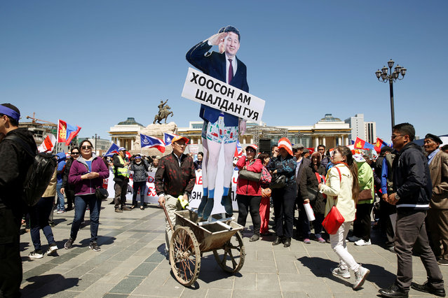 A protester pushes a cart with cut-outs of Mongolian Prime Minister Ukhnaa Khurelsukh during a demonstration demanding the Mongolian leadership to step down, in Ulaanbaatar, Mongolia on May 30, 2019. (Photo by Rentsendorj Bazarsukh/Reuters)