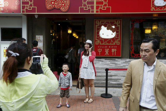 Customers take pictures as they wait for an available table outside a Hello Kitty-themed Chinese restaurant in Hong Kong, China May 21, 2015. (Photo by Bobby Yip/Reuters)