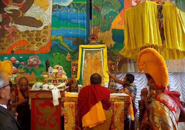 "Tibetan monks arrange the portrait of exiled Tibetan spiritual leader, the Dalai Lama, during a function organised to mark ""Losar"", or the Tibetan New Year, in Kathmandu, Nepal March 1, 2017. (Photo by Navesh Chitrakar/Reuters)"
