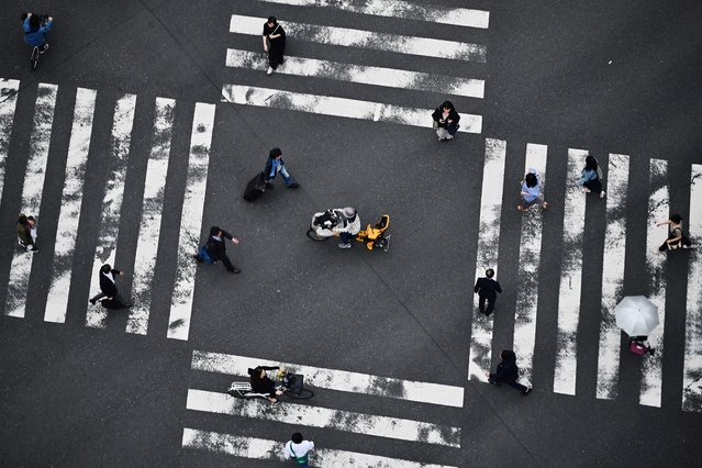 People cross a street in Tokyo's Ginza district on May 9, 2019. (Photo by Charly Triballeau/AFP Photo)