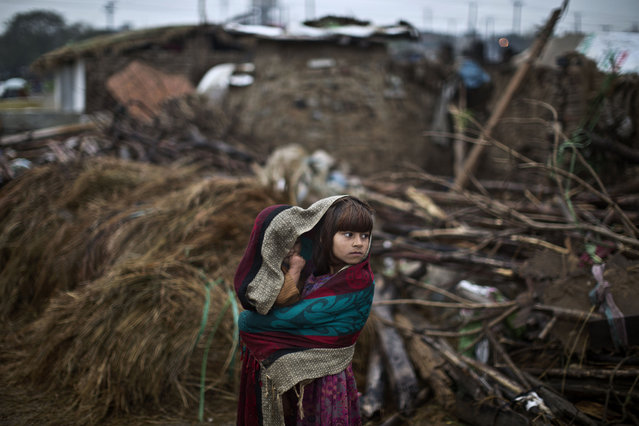 An Afghan refugee girl, wraps herself and her younger brother with a shawl to shield from the rain, while looking at mud houses of Afghan refugee families which were destroyed by the Capital Development Authority for being built on illegal lands, in a slum on the outskirts of Islamabad, Pakistan, Monday, March 24, 2014. Slums which are built on illegal lands have neither running water or sewage disposal. (Photo by Muhammed Muheisen/AP Photo)