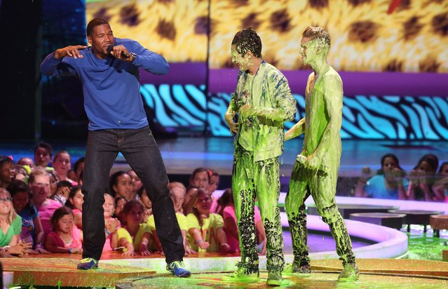 From left, Michael Strahan, speaks on stage, after Austin Mahone and Cody Simpson get slimed at the 27th annual Kids' Choice Awards at the Galen Center on Saturday, March 29, 2014, in Los Angeles. (Photo by Matt Sayles/Invision/AP Photo)