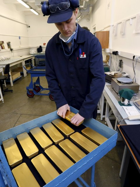 An employee takes an ingot of 99.99 percent gold for weighing and engraving at the Krastsvetmet Krasnoyarsk non-ferrous metals plant in the Siberian city of Krasnoyarsk, Russia, June 5, 2015. Krastsvetmet is one of the world's largest players in the precious metals industry. REUTERS/Ilya Naymushin