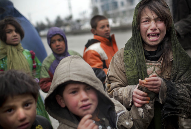 An Afghan refugee girl reacts after another child stole her food voucher while she was queuing in front a truck organized by the World Food Program in Kabul, on March 4, 2012. (Photo by Anja Niedringhaus/AP Photo)
