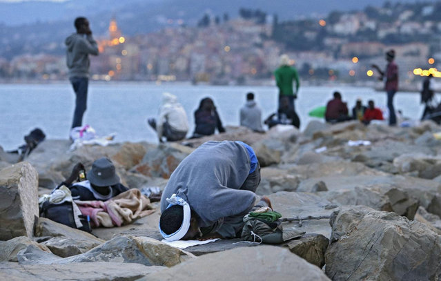 Migrant kneels in prayer, in Ventimiglia, at the Italian-French border Tuesday, June 16, 2015. Police at Italy's Mediterranean border with France forcibly removed a few dozen African migrants who have been camping out for days in hopes of continuing their journeys farther north, a violent scene Italy is using to show that Europe needs to do something about the migrant crisis. (AP Photo/Lionel Cironneau)