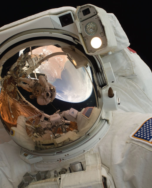 A close-up of Astronaut John Grunsfeld shows the reflection of Astronaut Andrew Feustel, perched on the robotic arm and taking the photo. The pair teamed together on three of the five spacewalks during Servicing Mission 4 in May 2009. (Photo by NASA)