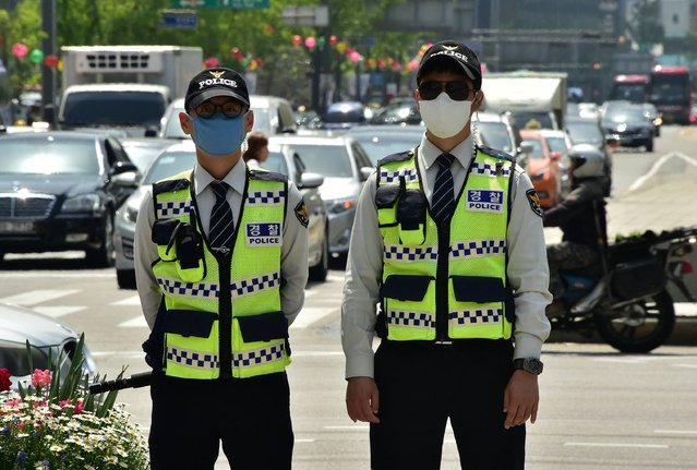 South Korean policemen wearing protective masks stand guard on a street in central Seoul on April 25, 2016. South Korean officials are advising the public to refrain from outdoor activities and to wear a protective mask when they go outside as air quality across the country continues to be affected by high levels of both fine and yellow dust. (Photo by Jung Yeon-Je/AFP Photo)