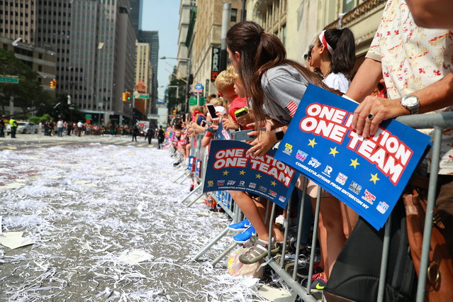 Fans celebrate as members of the the U.S. women's soccer team pass by during a ticker tape parade along the Canyon of Heroes, Wednesday, July 10, 2019, in New York. (Photo by Gordon Donovan/Yahoo News)